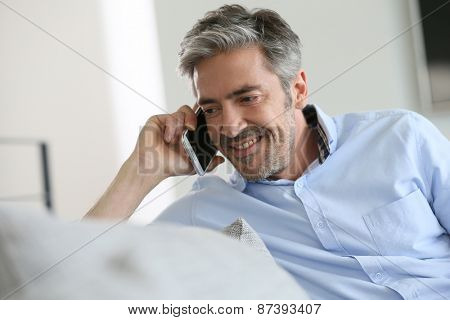Mature man sitting in sofa and talking on phone