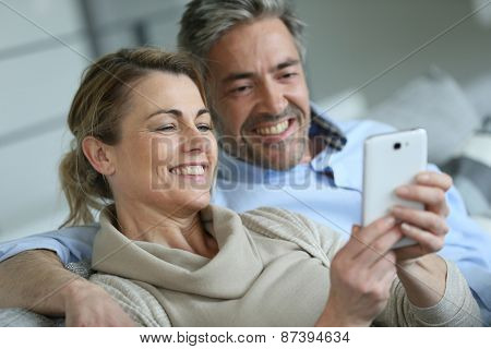 Mature coupel sittign in sofa and using smartphone