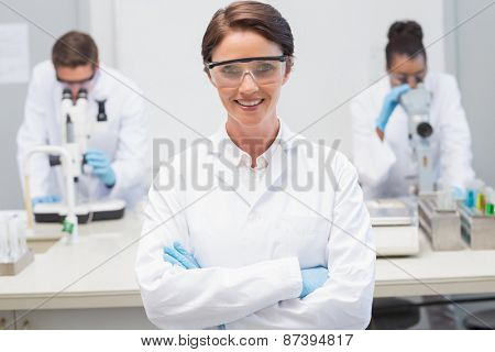 Happy scientist smiling at camera with protective glasses in the laboratory