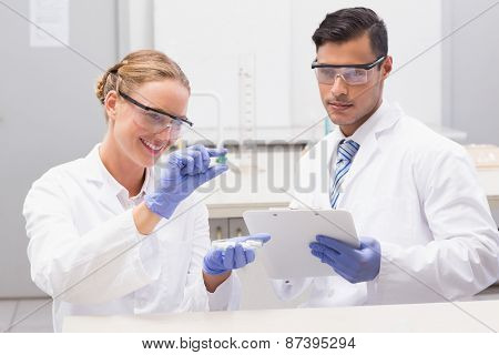 Scientists looking at petri dish and taking notes in laboratory