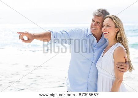 Happy couple standing by the sea and pointing something at the beach