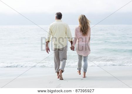 Happy couple walking by the sea at the beach