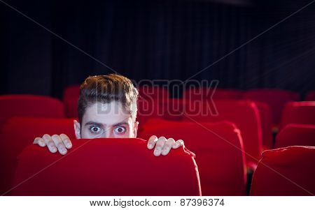 Young man watching a scary film at the cinema