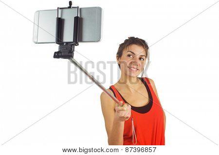 Casual brunette using selfie stick shot in studio