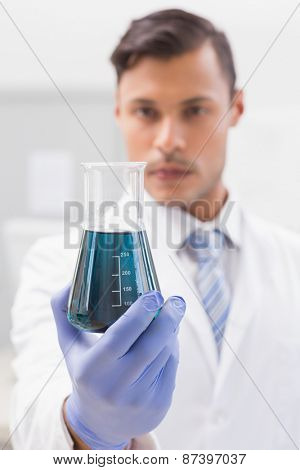 Concentrated scientist looking at beaker in laboratory
