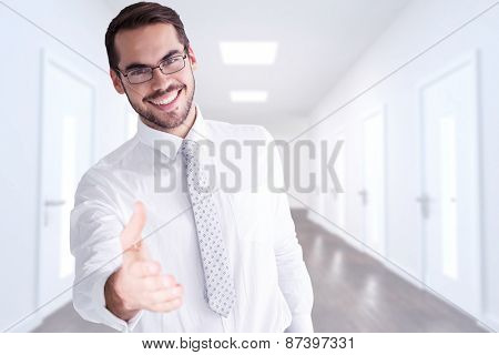 Happy businessman with glasses offering handshake against bright hallway with several doors