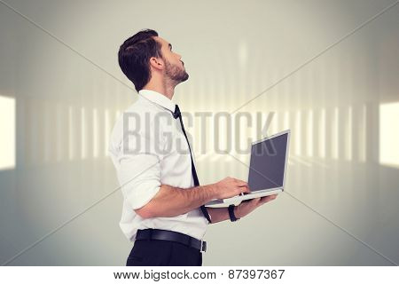 Sophisticated businessman standing using a laptop against white curved room with light