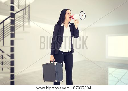 Pretty businesswoman shouting with megaphone against digitally generated room with winding stairs