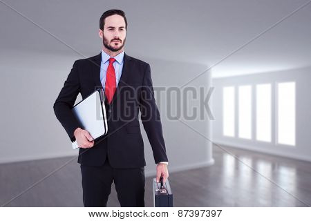 Handsome businessman holding briefcase and laptop against bright room with wall in the middle