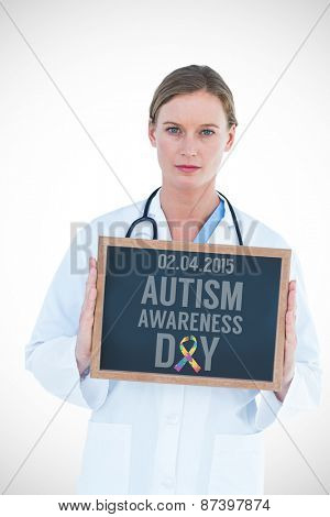 Doctor showing chalkboard against autism awareness day