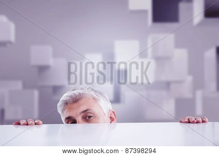 Businessman peeking over desk against abstract white room