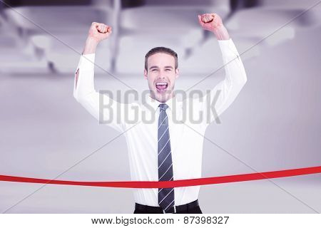 Businessman crossing the finish line and cheering against white abstract room