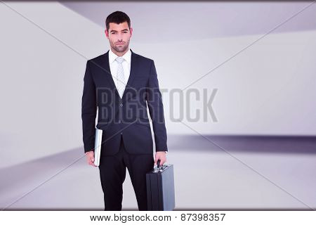 Businessman standing with his briefcase and documents against abstract room