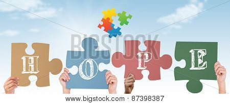 Hands holding up hope jigsaw pieces against blue sky