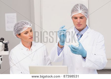 Scientists working attentively with beaker in laboratory