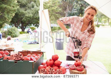 Woman Juicing Fresh Pomegranates At Farmers Market Stall