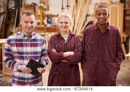 Portrait Of Carpenter With Apprentices In Furniture Workshop