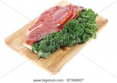 fresh raw beef meat fillet with red hot chili pepper and raw kale leafs on wooden board isolated over white background