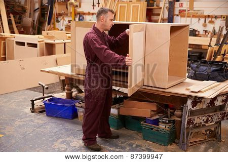 Carpenter Building Furniture In Workshop