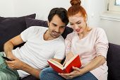 foto of settee  - Young Couple Resting on the Sofa at the Living Room While the Man is Watching TV and Woman is Reading a Book - JPG