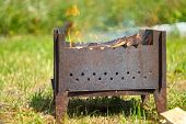 picture of brazier  - Iron brazier with burning fire wood stands on the grass. ** Note: Shallow depth of field - JPG