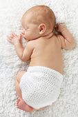 foto of baby diapers  - Newborn baby boy sleeping wearing a knitted diaper cover - JPG