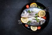 pic of bass fish  - Raw fish with ingredients in the pan on dark background with blank space - JPG