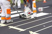 image of pedestrian crossing  - Two workers making of a new pedestrian crossing on the road - JPG
