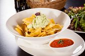 image of nachos  - Crisp corn nachos with spicy fresh guacamole sauce and a topping of avocado served as a snack or appetizer in a white bowl - JPG