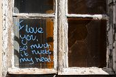 picture of abandoned house  - Old broken grunge part of weathered window of abandoned house with funny graffiti notice on glass - JPG
