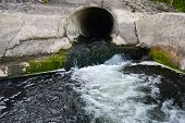 pic of sewage  - Filth flowing out from sewage pipe angle shot - JPG