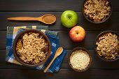 foto of crisps  - Overhead shot of three rustic bowls of baked apple crumble or crisp spoonful of cinnamon powder fresh apples and raw rolled oats on the side photographed on dark wood with natural light - JPG