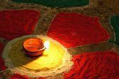 stock photo of rangoli  - oil lamp at center of colorful rangoli - JPG