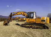 stock photo of excavator  - Old and rusty excavators digging out pebbles from the bank of the river one excavator - JPG