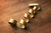 pic of coil  - Coiled gold ribbon on rustic or aged old wooden desk - JPG