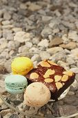 foto of brownie  - Brownies with Macaron in a dish on the background of rocks - JPG