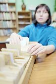 image of librarian  - Librarian woman searches something in card catalog - JPG