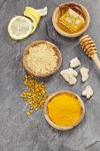 stock photo of granite  - Natural remedies. Ginger powder, root and turmeric pieces, powder and honeycomb in olive wood bowls, for alternative medicine ,spa products and food ingredients, over dark granite table. Macro photograph, selective focus