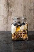 foto of muse  - A jar of healthy swiss museli yogurg blackberries and honey on a black slate background - JPG