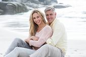 stock photo of couple sitting beach  - Happy couple sitting on the sand at the beach - JPG