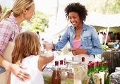 picture of stall  - Woman Selling Soft Drinks At Farmers Market Stall - JPG