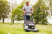 picture of grass-cutter  - Man Working In Garden Cutting Grass With Lawn Mower - JPG