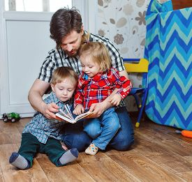 picture of father child  - Father and children brother and sister reading a book sitting on the floor in the nursery - JPG
