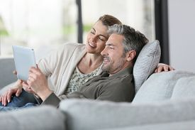 picture of mature adult  - Mature couple using digital tablet relaxing in sofa - JPG