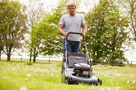 image of grass-cutter  - Man Working In Garden Cutting Grass With Lawn Mower - JPG