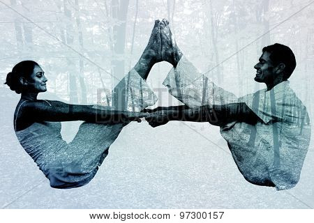 Peaceful couple sitting in boat position together against trees in the autumnal forest
