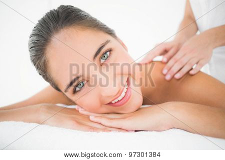 Close up of an attractive young woman receiving back massage at spa center