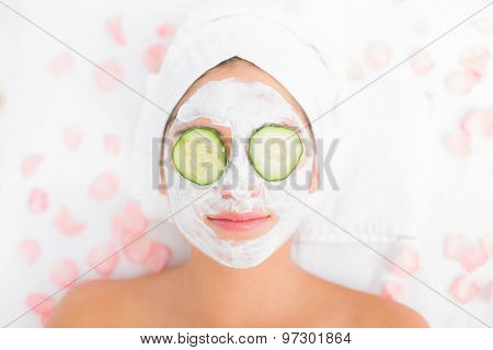 Attractive woman having cucumber on her face at spa center