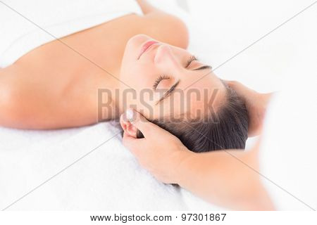 Close up of an attractive young woman receiving head massage at spa center