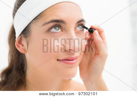 Close up of a hand applying mascara to beautiful woman